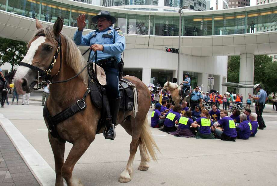 Police push bystanders back on Wednesday after 15 protesters were arrested while sitting in the circle at Smith and Bell downtown. The Service Employees International Union wants janitors' wages raised to $10 an hour. Photo: J. Patric Schneider / Houston Chronicle