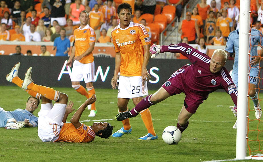Sporting KC goalkeeper Jimmy Nielsen dives for the ball as forward Calen Carr, center on ground, deflected the ball into the goal as Sporting KC defender Matt Besler,  forward Brian Ching and midfielder Brad Davis looked on. Photo: Johnny Hanson, Houston Chronicle / © 2012  Houston Chronicle