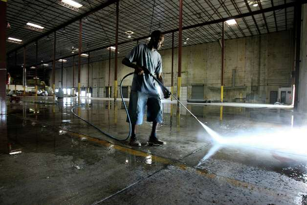Matthew Jones power washes the floor at the new  distribution headquarters for Daily Bread Ministries on Thursday July 12, 2012.  The program is relocating its food distribution headquarters from downtown to a warehouse on Rittiman Road.  It provides 163,000 square feet compared to its old location with nearly 6,300.  The nonprofit ministry is planning to dedicate the space on Saturday July 21. Photo: Helen L. Montoya, San Antonio Express-News / ©SAN ANTONIO EXPRESS-NEWS