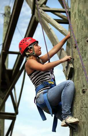 Lexi Mahone, of Dallas, climbs a pole on a high ropes course which ends with a ride on a zipline.  Campers from all over Texas take part in the Texas Burn Survivor Society's Pediatric Burn Camp, called Camp David, held at Texas Lion's Camp in Kerrville, TX.  Wednesday, July 18, 2012. Photo: Bob Owen, San Antonio Express-News / © 2012 San Antonio Express-News