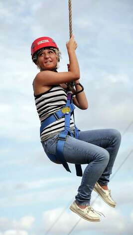 Lexi Mahone, of Dallas, rides on a zipline.  Campers from all over Texas take part in the Texas Burn Survivor Society's Pediatric Burn Camp, called Camp David, held at Texas Lion's Camp in Kerrville, TX.  Wednesday, July 18, 2012.  Mahone was injured in a fire when she was 3 years old. Photo: Bob Owen, San Antonio Express-News / © 2012 San Antonio Express-News