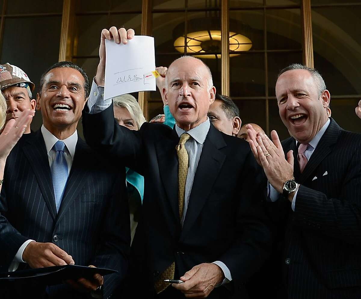 Gov. Jerry Brown (center) holds up a legislation which he signed authorizing initial construction of California's $68 billion high-speed rail line with Los Angeles Mayor Antonio Villaraigosa (left) and state and city officials looking at Union Station on July 18, 2012 in Los Angeles, California. The bill authorizes $10 billion in state bonds to start construction of a high-speed rail line between Los Angeles and San Francisco.