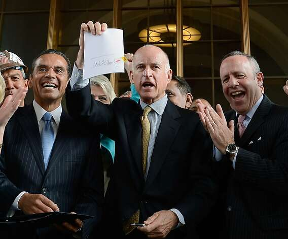 Gov. Jerry Brown (center) holds up a legislation which he signed authorizing initial construction of California's $68 billion high-speed rail line with Los Angeles Mayor Antonio Villaraigosa (left) and state and city officials looking at Union Station on July 18, 2012 in Los Angeles, California. The bill authorizes $10 billion in state bonds to start construction of a high-speed rail line between Los Angeles and San Francisco. Photo: Kevork Djansezian, Getty Images