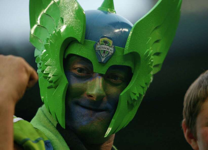 A fan is shown with a painted face and Sounders costume during the Sounders vs. Chelsea game at Cent