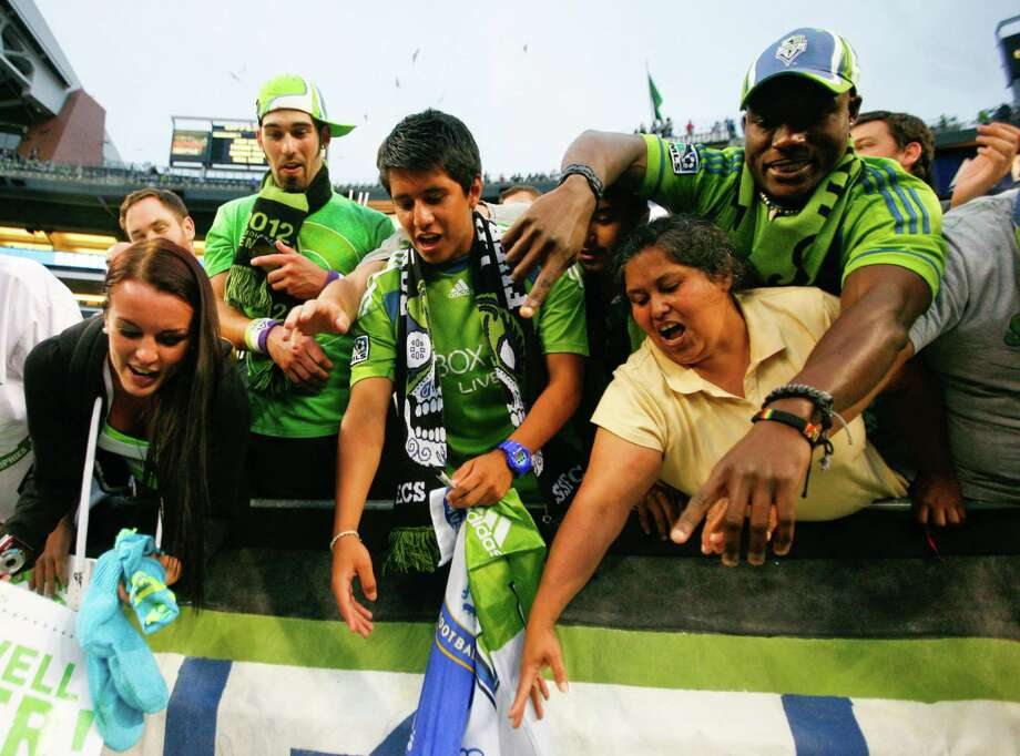 Fans reach for sounders player, Roger Levesque, as he prepares to give away his shoes after the Sounders vs. Chelsea game at CenturyLink field in Seattle on Wednesday, July 18, 2012. The Sounders were defeated 2-4. Photo: Sofia Jaramillo / SEATTLEPI.COM