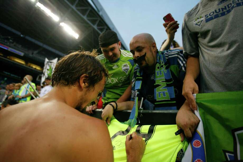 Sounders player, Roger Levesque, signs a t-shirts for fans after the Sounders vs. Chelsea game at CenturyLink field in Seattle on Wednesday, July 18, 2012. This was Roger Levesque's last game with the sounders. The Sounders were defeated 2-4. Photo: Sofia Jaramillo / SEATTLEPI.COM