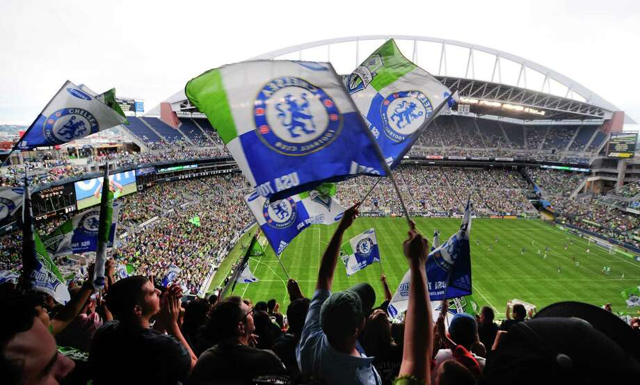 Fans wave their commemorative flags as the Sounders score during an international friendly match between the Seattle Sounders FC and the UK's Chelsea FC on Wednesday, July 18, 2012 at CenturyLink Field. Chelsea won 4-2 to a crowd of 53,309 in a game that was Sounders'  Roger Levesque's last professional match. Photo: LINDSEY WASSON / SEATTLEPI.COM