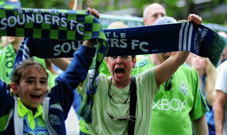 Fans yell as they hold their Sounders scarves on a march from Occidental Park to CenturyLink  before an international friendly match between the Seattle Sounders FC and the UK's Chelsea FC on Wednesday, July 18, 2012. Chelsea won 4-2 to a crowd of 53,309 in a game that was Sounders'  Roger Levesque's last professional match. Photo: LINDSEY WASSON / SEATTLEPI.COM