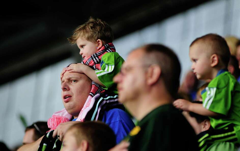 A young fan watches the game from her father's shoulders during an international friendly match betw