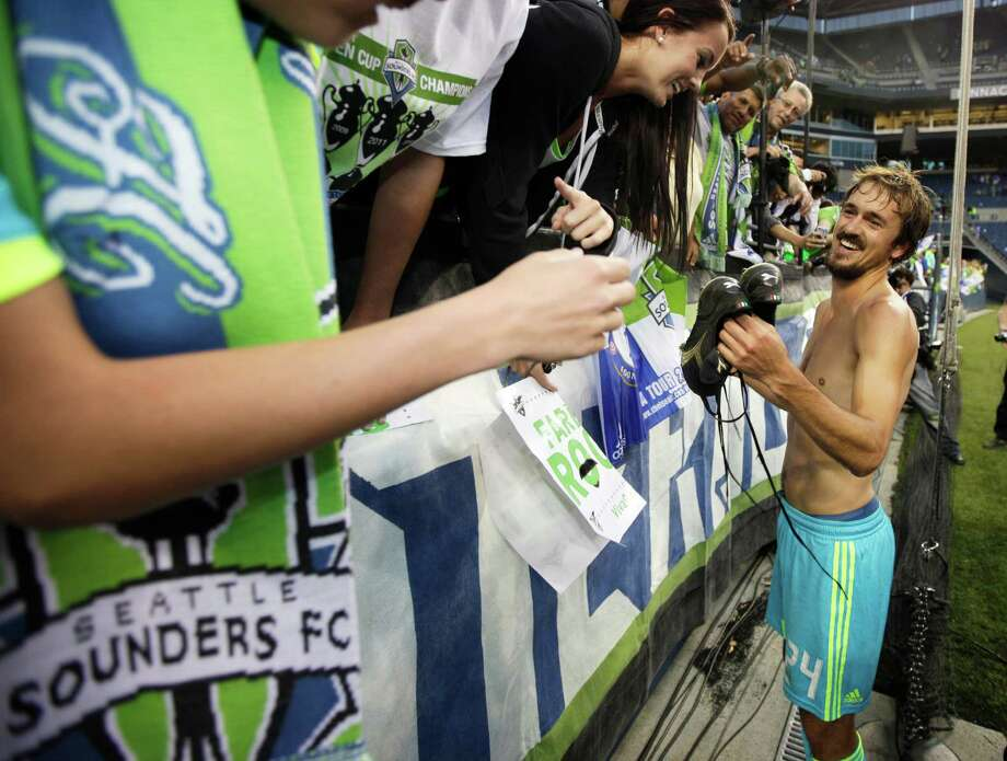Seattle Sounders' Roger Levesque gives away his cleats following an exhibition match against Chelsea, Wednesday, July 18, 2012, in Seattle. Levesque retired following the match, which Chelsea won, 4-2. Photo: AP