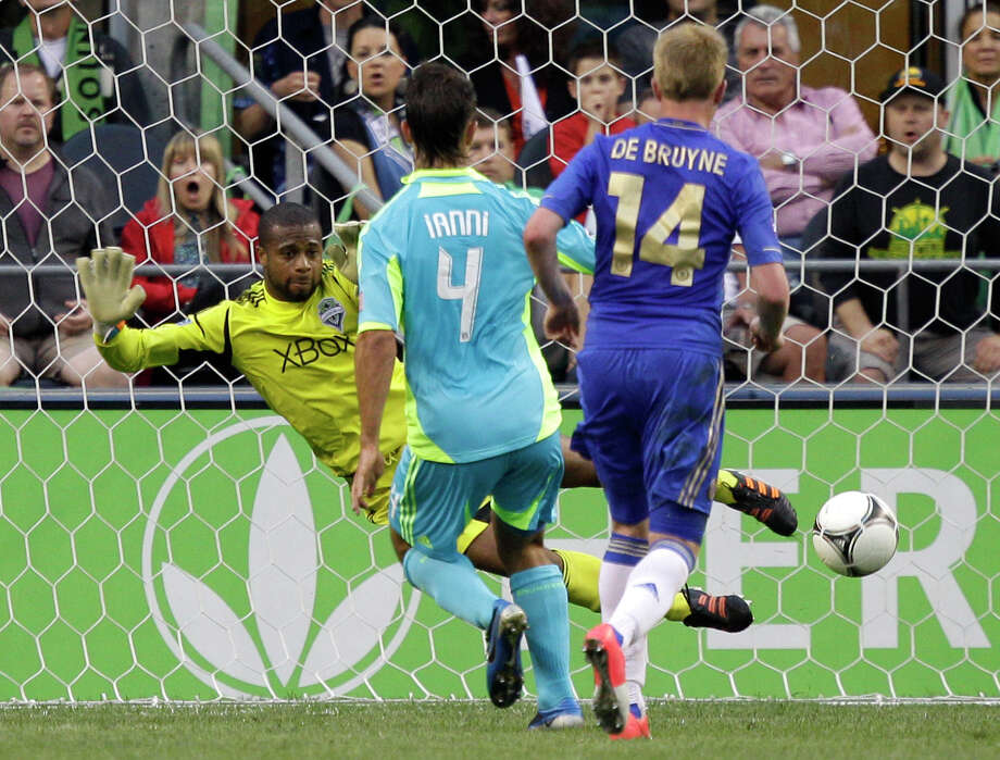 Seattle Sounders goalkeeper Josh Ford, left, deflects a Chelsea shot with his feet as Sounders' Patrick Ianni (4) and Chelsea's Kevin De Bruyne (14) look on in the second half of an exhibition match, Wednesday, July 18, 2012, in Seattle. Chelsea beat the Sounders, 4-2. Photo: AP