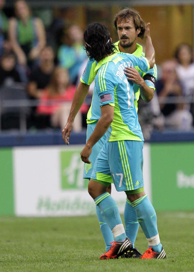 Seattle Sounders' Fredy Montero, left, greets Roger Levesque, right, as Montero leaves the field during the second half of an exhibition match against Chelsea, Wednesday, July 18, 2012, in Seattle. Levesque retired following the match. Photo: AP