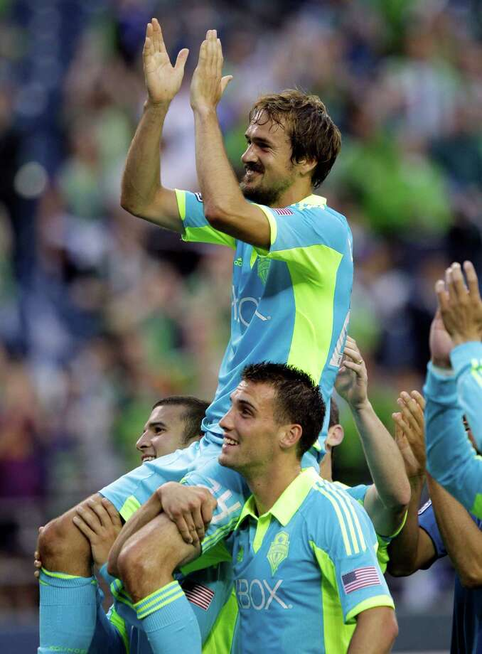 Seattle Sounders' Roger Levesque is lifted on the shoulders of Michael Seamon, right, and Servando Carrasco, left, following an exhibition soccer match against Chelsea, Wednesday, July 18, 2012, in Seattle. Levesque retired following the match. Photo: AP