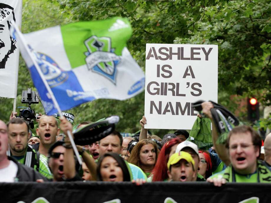 "Seattle Seahawks supporters carry a sign that reads ""Ashley is a Girl's Name,"" in reference to Chelsea defender Ashley Cole, as they march before an exhibition soccer match between Chelsea and the Seattle Sounders, Wednesday, July 18, 2012, in Seattle. Photo: AP"