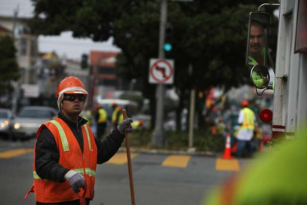 Timo Failauga (l to r) works along the median on Geary Boulevard as Lisandro Ponce, Recology driver, moves the truck along to pick up the plants and debris being removed on Thursday, July 12, 2012 in San Francisco, Calif. Photo: Lea Suzuki, The Chronicle