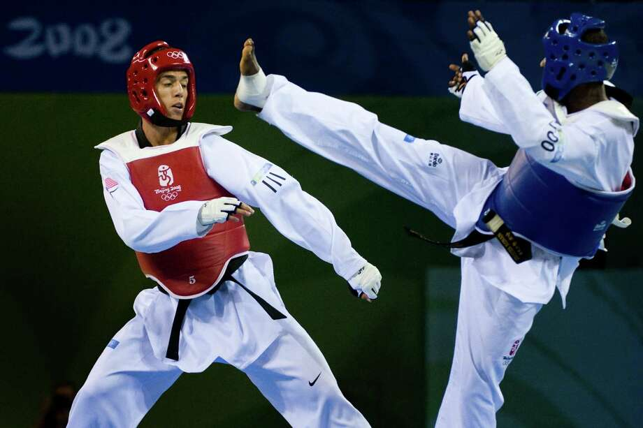 Steven Lopez of Sugar Land, in red, fights N'guessan Sebastien Konan during a 80kg taekwondo matchup at the 2008 Summer Olympic Games in Beijing. Photo: Smiley N. Pool, Houston Chronicle / Houston Chronicle