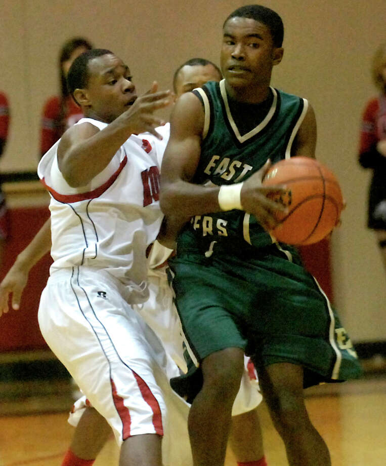 East Chambers' Jared Guillory tries to swing around Kountze's Justin Harper at Kountze High School in Kountze, Friday, January 27, 2012. Tammy McKinley/The Enterprise Photo: TAMMY MCKINLEY