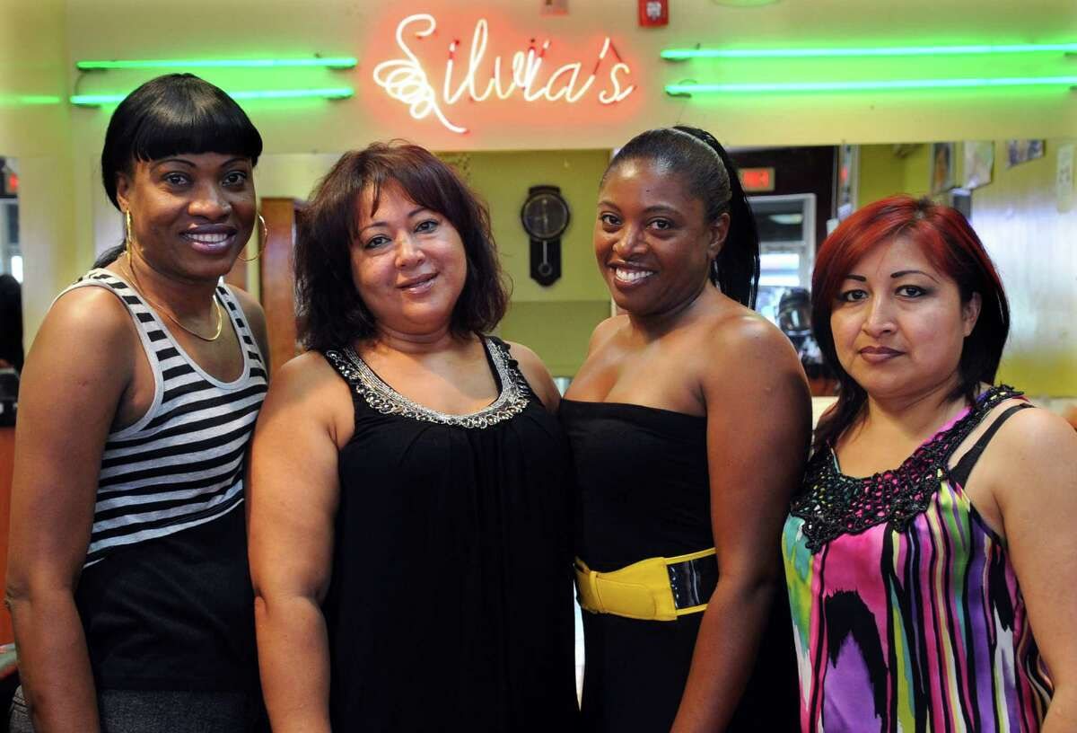 From left, hairdresser Fabiola Placide, owner Silvia Torres, and hairdressers Alyda Haynes and Nancy Loja, pose for a photo at Why Not Silvia's beauty salon on East Main Street in Stamford on July 19, 2012.
