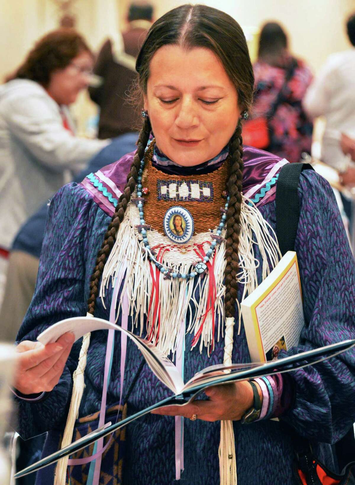 Julienne Montour of Taylor, Mich. looks at a book about Kateri Tekakwitha, at the 73rd Annual Tekakwitha Conference in Colonie on Thursday, July 19, 2012. (John Carl D'Annibale / Times Union)