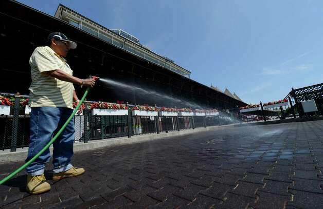 Armando Pardo washes down the winner's circle in preparation for the 144th opening day at the Saratoga Race Course in Saratoga Springs, N.Y. July 19, 2012.   (Skip Dickstein/Times Union) Photo: Skip Dickstein