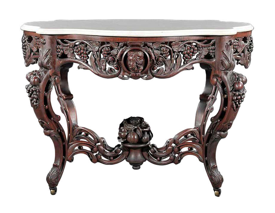 This table sold at a Neal Auction in New Orleans in April 2012, for $27,060. The heads carved into the wooden edge of the table top were the clue to the maker. It is attributed to John Henry Belter. Photo: Contributed Photo
