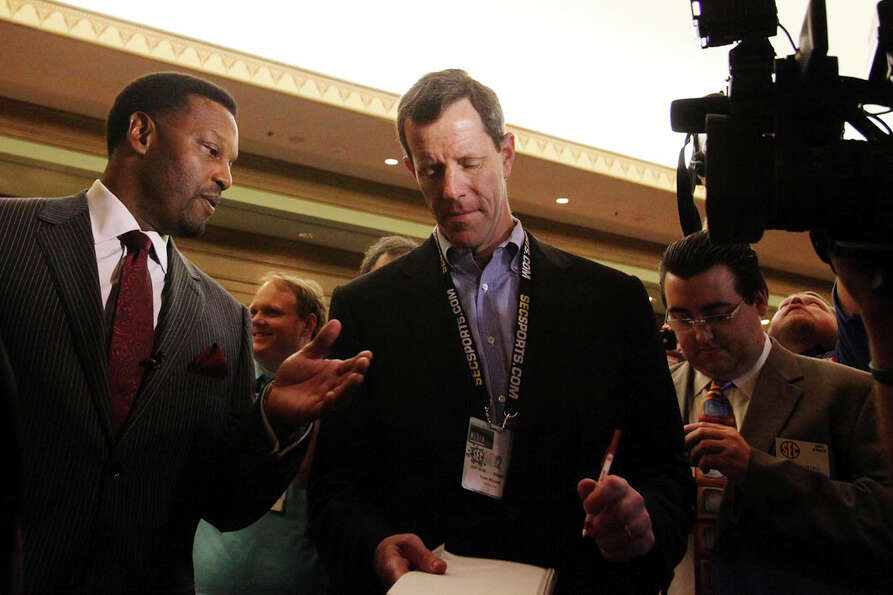 Texas A&M coach Kevin Sumlin, left, talks to reporters at the Southeastern Conference NCAA college f