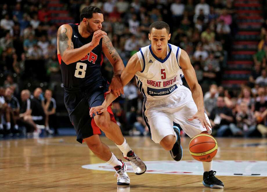 Great Britain's Andrew Lawrence, right, gets past USA's Deron Williams during an Olympic Warm Up match against the USA at the Manchester Arena, Manchester Thursday July 19, 2012.    (AP Photo/ Dave Thompson/PA Wire)  UNITED KINGDOM OUT NO SALES NO ARCHIVE Photo: Dave Thompson, Associated Press / PA