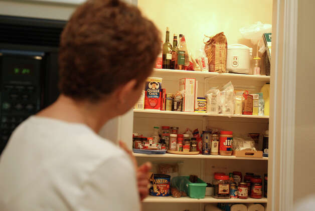 Janet Faust peers into her pantry for staple items she always has Tuesday July 3, 2012 in her kitchen. Photo: Julysa Sosa / SAN ANTONIO EXPRESS-NEWS