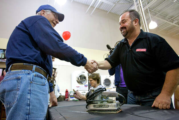 "In this photo taken by AP Images for Craftsman, Frank Fritz, right, a famous treasure hunter from the T.V. show, ""American Pickers"" shakes hands with Mike Clemence of Clinton, Iowa after examining an old Craftsman sander he brought to the Craftsman Finding America's Treasures event at the Sears Hometown Store in Clinton, Iowa on Saturday, May 7, 2011. (Mark Hirsch/AP Images for Craftsman) Photo: Mark Hirsch"