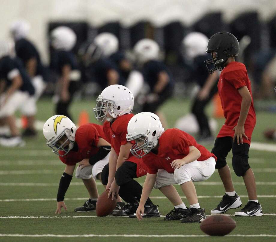 Participants line up as they practice a drill during the Houston Texans' Youth Football Camp at Methodist Training Center. The camp is open to children ages 8 to 14. Photo: Karen Warren / © 2012  Houston Chronicle