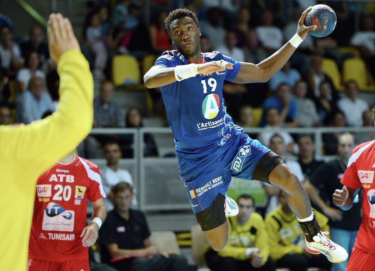 France's player Luc Abalo (R) shoots to Tunisia's goalkeeper on July 13, 2012 in Strasbourg, eastern France, during the