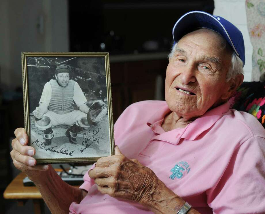 Former major league baseball player, Mike Sandlock, 96, holds a 1945 photo of himself as a catcher with the Brooklyn Dodgers behind the plate at Ebbets Field in Brooklyn, in his Cos Cob home, Thursday, July 19, 2012. Photo: Bob Luckey / Greenwich Time