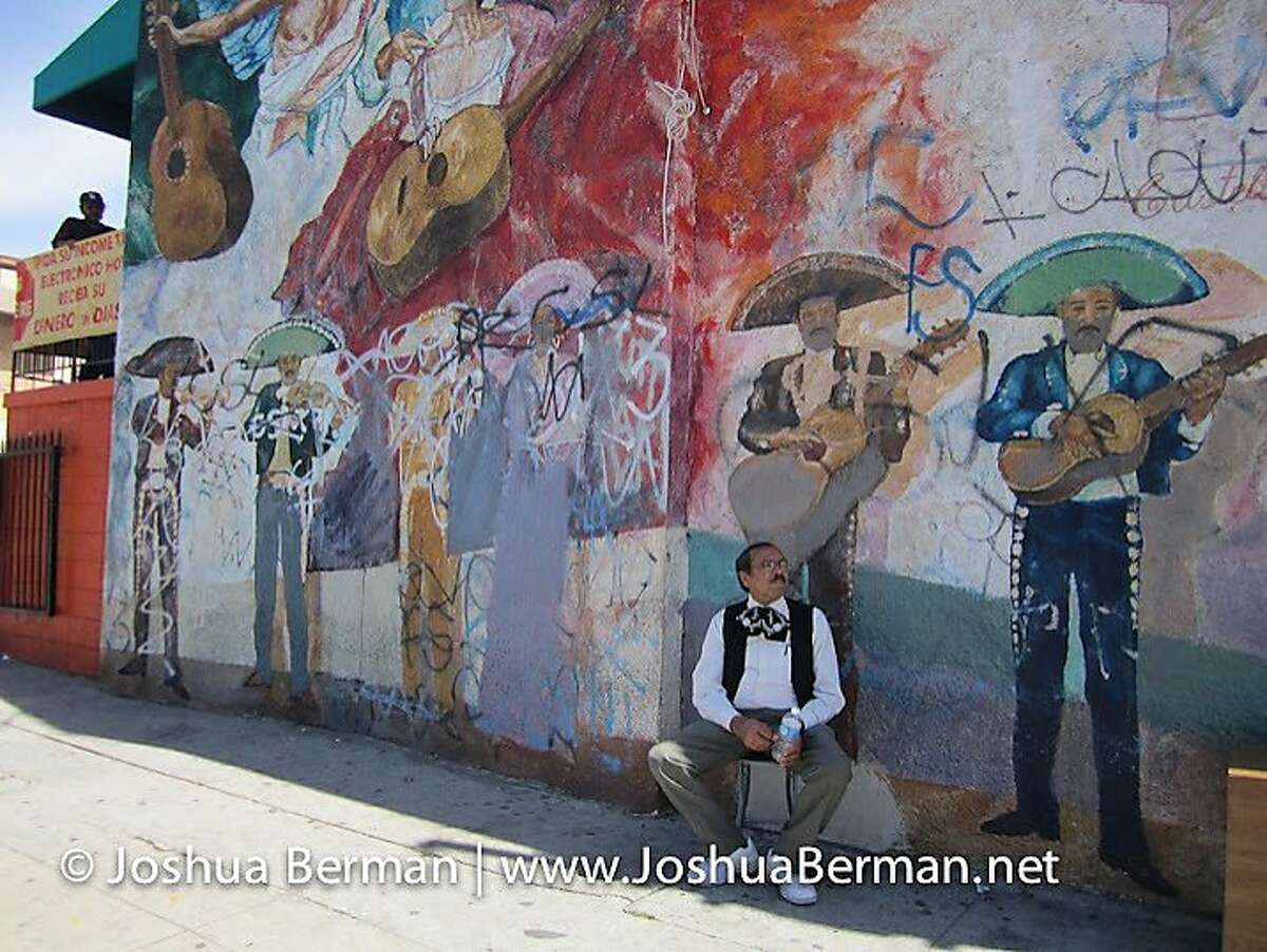 A musician sits below a mural in Mariachi Plaza de Los Angeles (in East Los Angeles), a public square dedicated to mariachi and its players.