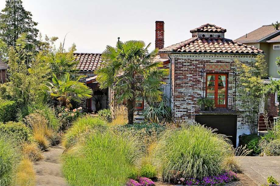 Looking for a change from the everyday Seattle home? Check out this eclectic Spanish-style brick house built in 1931 in West Seattle's Gatewood neighborhood. The house, 6923 40th Ave. S.W., is 3,320 square feet, with three bedrooms, 1.75 bathrooms, exposed beams, leaded glass, Spanish tile, a family room, a wine cellar, an office and a patio on a 5,801-square-foot lot. It's listed for $949,000. Photo: Courtesy Dawn Leverett/Windermere Real Estate