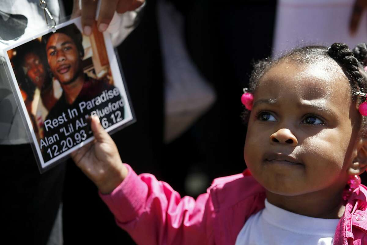 Camari Carter, 2 years old, pulls on a tag worn by her mother of Alan Blueford, as the family addresses the media outside the Alameda County Sheriffs Coroner's Office, Thursday July 19, 2012 in Oakland, Calif. The Blueford family are asking for a copy of their son Alan Blueford's autopsy report and demanding justice for his killing. Alan, 18 years old, was killed on May 6th by an Oakland police office in East Oakland.