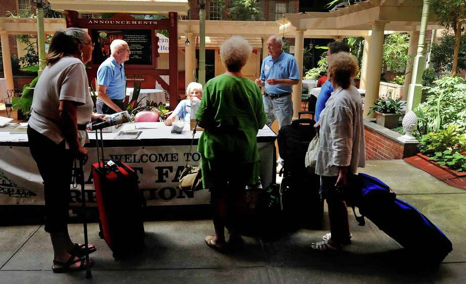 Dick Bratt, second from left, and his wife Barb Bratt, third from left, from Syracuse check in fellow Bradt descendants at the Desmond Hotel on Thursday, July 19, 2012 in Colonie, NY.  Descendants of the Bradts, a family that arrived in Rensselaerswyck in 1637 and have a 375-year connection to Albany, are in town for the fifth family reunion.   (Paul Buckowski / Times Union) Photo: Paul Buckowski