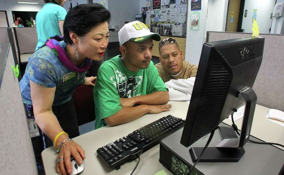 FILE- In this Tuesday, July 17, 2012, file photo, Career center specialist Sun Gaddis, left, helps job seeker Kaston Joshua, center, while Rudy Martin looks on at WorkSource Oregon Tuesday,  in Tualatin, Ore. number of Americans seeking unemployment benefits rose by 34,000 last week, a figure that may have been skewed higher by seasonal factors. Applications for benefits increased to a seasonally adjusted 386,000, the Labor Department said Thursday, July 19, 2012. The gain followed a drop of 24,000 the previous week and was the biggest jump since April 2011.(AP Photo/Rick Bowmer, File) Photo: Rick Bowmer, AP / AP