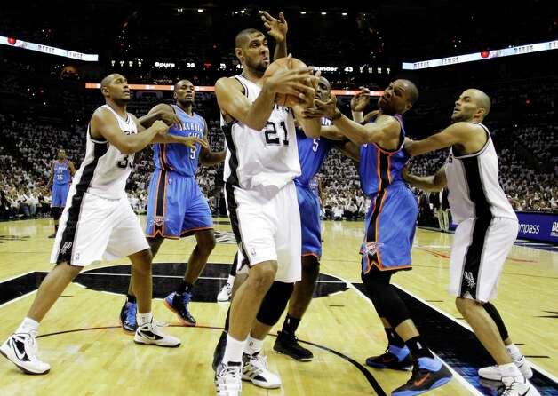 San Antonio Spurs center Tim Duncan (21) grabs a rebound as Oklahoma City Thunder center Kendrick Perkins (5) and point guard Russell Westbrook defend during the first half of Game 5 in the NBA basketball Western Conference finals, Monday, June 4, 2012, in San Antonio. Spurs power forward Boris Diaw (33), of France, Thunder power forward Serge Ibaka (9), from the Republic of Congo, and Spurs point guard Tony Parker, left, of France, watch the action. (AP Photo/Eric Gay) Photo: Eric Gay, STF / AP