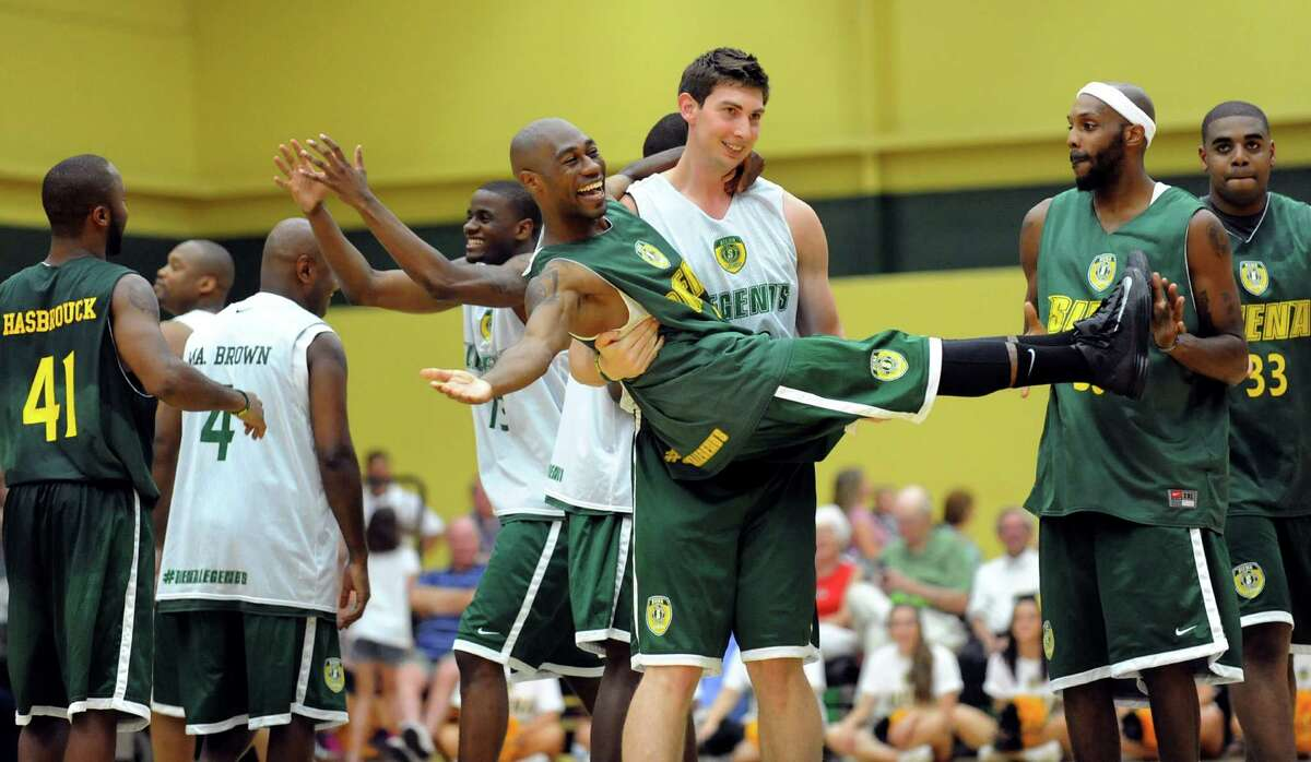Ryan Rossiter, center, picks up Tay Fisher when the opposing teams greet each other at the start of the Siena Legends basketball game on Thursday, July 19, 2012, at Siena College in Loudenville, N.Y. (Cindy Schultz / Times Union)