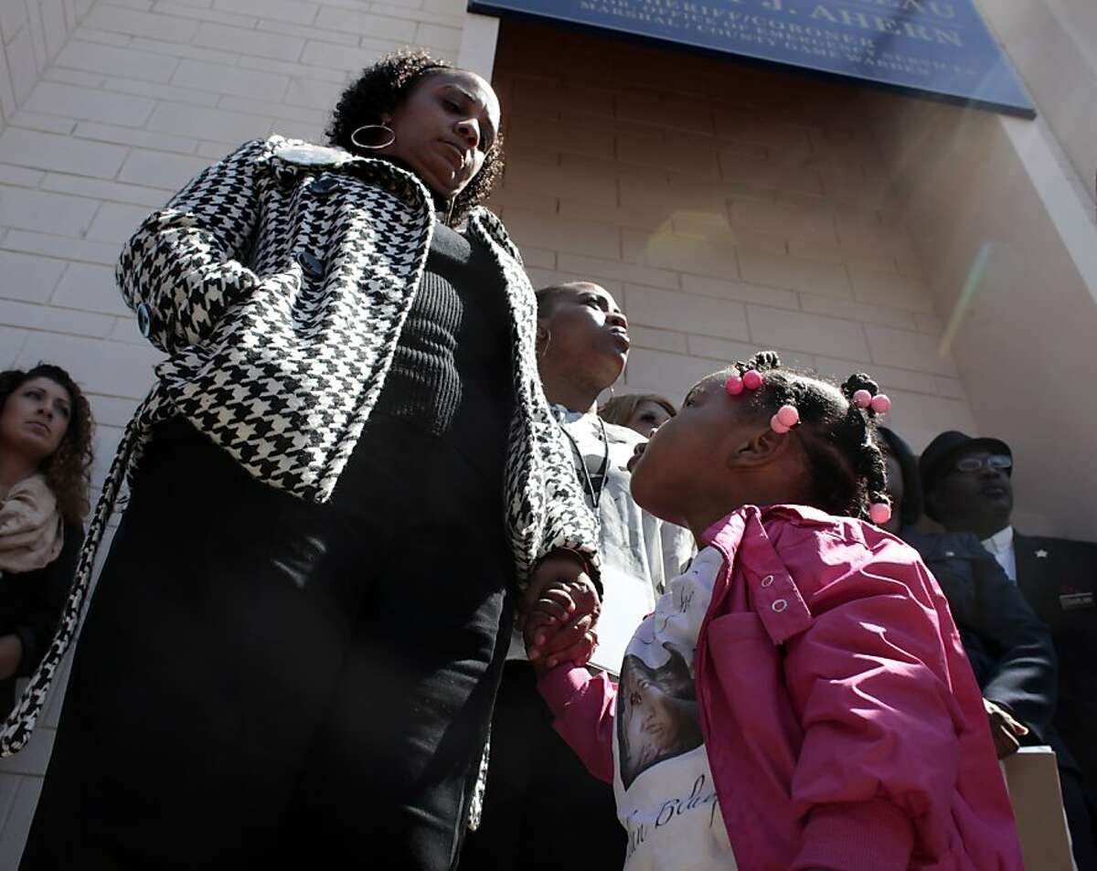 Camari Cater, 2 years old, looks up to her grandmother Jeralynn Blueford outside the Alameda County Sheriffs Coroner's Office as the family addresses the media, Thursday July 19, 2012 in Oakland, Calif. The Blueford family are asking for a copy of their son Alan Blueford's autopsy report and demanding justice for his killing. Alan, 18 years old was killed on May 6th by an Oakland police office in East Oakland.