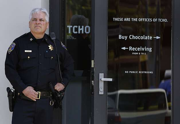 A police captain stands in front of the TCHO chocolate factory entrance while officers investigate a stabbing incident after one employee stabbed another in San Francisco, Calif. on Wednesday, July 18, 2012. The suspect was later shot and wounded by officers at Washington and Davis streets, several blocks away. Photo: Paul Chinn, The Chronicle