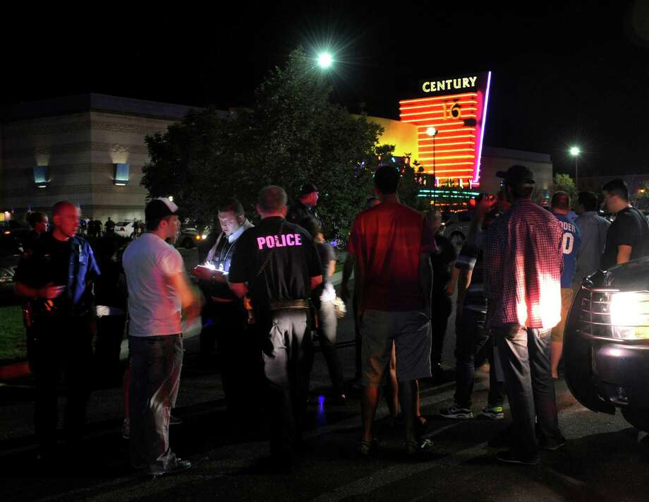 Police officers took witness statements outside a move theatre in Aurora, Colorado following an early morning shooting. Aurora Police responded to the Century 16 movie theatre early Friday morning, July 20, 2012.  Scanner traffic indicates that dozens of people were hurt in an incident inside the theatre. Photo: Karl Gehring/The Denver Post