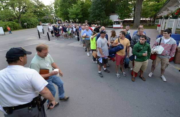 Hundreds of racing fans line up in front of the Saratoga Race Course gates some as early as 3:00 am on opening day July 20, 2012.  They were waiting for their chance to get a picnic table or two under the trees for their day at the races.  (Skip Dickstein / Times Union) Photo: SKIP DICKSTEIN