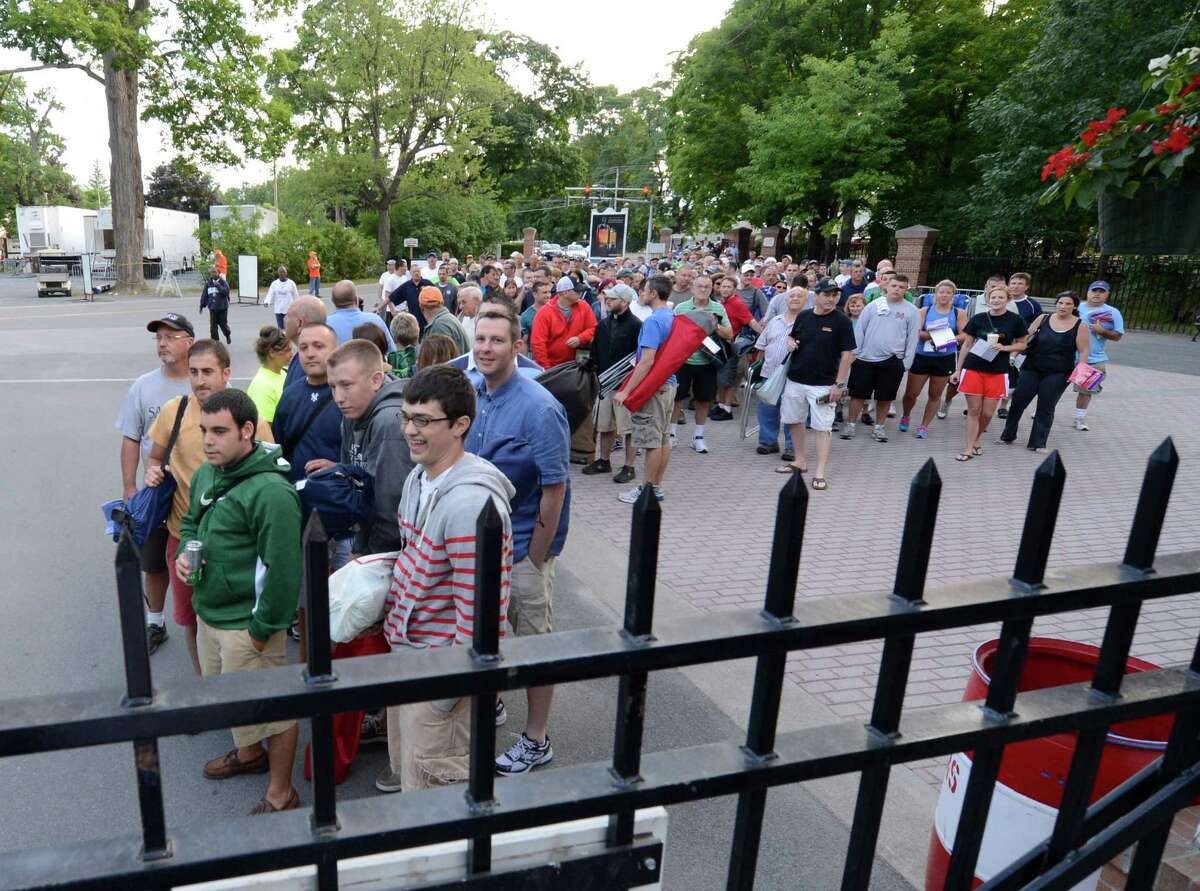 Hundreds of racing fans line up in front of the Saratoga Race Course gates some as early as 3:00 am on opening day July 20, 2012. They were waiting for their chance to get a picnic table or two under the trees for their day at the races. (Skip Dickstein / Times Union)