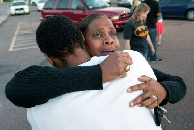 "Shamecca Davis hugs her son Isaiah Bow, who was an eye witness to the shooting, outside Gateway High School where witness were brought for questioning Friday, July 20, 2012 in Denver.  After leaving the theater Bow went back in to find his girlfriend. "" I didn't want to leave her in there. But she's ok now,"" Bow said.   A gunman wearing a gas mask set off an unknown gas and fired into a crowded movie theater at a midnight opening of the Batman movie ""The Dark Knight Rises,"" killing at least 12 people and injuring at least 50 others, authorities said. (AP Photo/Barry Gutierrez) Photo: Barry Gutierrez, ASSOCIATED PRESS / AP2012"