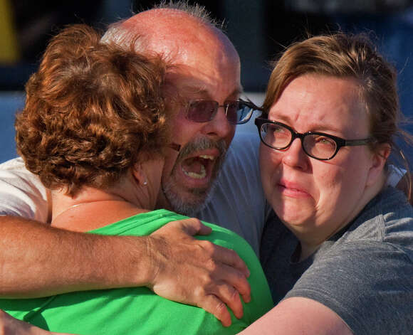 "Tom Sullivan, center, embraces family members outside Gateway High School where he has been searching frantically for his son Alex Sullivan who celebrated his 27th birthday by going to see ""The Dark Knight Rises,"" movie where a gunman opened fire Friday, July 20, 2012, in Aurora, Colo. (AP Photo/"