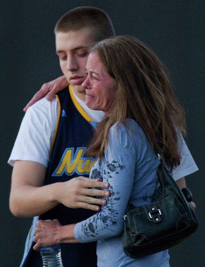 """Jacob Stevens, 18, hugs his mother Tammi Stevens after being interview by police outside Gateway High School where witness were brought for questioning after a shooting at a movie theater, Friday, July 20, 2012 in Denver. A gunman wearing a gas mask set off an unknown gas and fired into a crowded movie theater at a midnight opening of the Batman movie """"The Dark Knight Rises,"""" killing at least 12 people and injuring at least 50 others, authorities said. (AP Photo/Barry Gutierrez) Photo: Barry Gutierrez, ASSOCIATED PRESS / AP2012"""