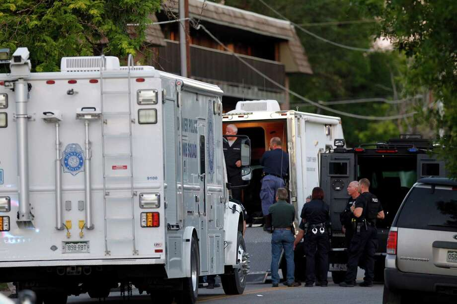 Police gather near an apartment house where the suspect in a shooting at a movie theatre lived in Aurora, Colo., Friday, July 20, 2012. As many as 14 people were killed and 50 injured at a shooting at the Century 16 movie theatre early Friday during the showing of the latest Batman movie. (AP Photo/Ed Andrieski) Photo: Ed Andrieski, ASSOCIATED PRESS / AP2012