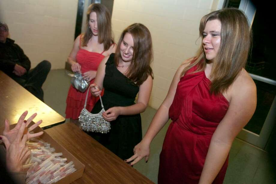 From left, Veronica Colacurcio, 15, Emily Katz, 15, and Samantha Gronberg, r15, right, check in where all students were given hand sanitizer as a precaution against the H1N1 flu before the homecoming dance at Stamford High School in Stamford, Conn. on Wednesday, Nov. 25, 2009. Photo: Chris Preovolos / Stamford Advocate