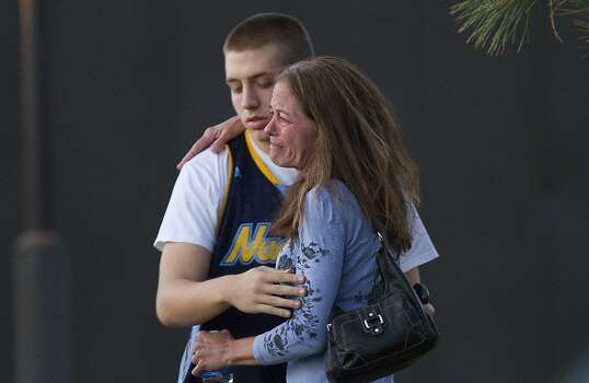 Eyewitness Jacob Stevens, 18, hugs his mother Tammi Stevens after being interview by police outside Gateway High School where witnesses were brought for questioning Friday, July 20, 2012 in Aurora, Colo.  A gunman wearing a gas mask set off an unknown gas and fired into the crowded movie theater killing 12 people and injuring at least 50 others, authorities said. (AP Photo/Barry Gutierrez) Photo: Barry Gutierrez, Associated Press